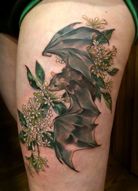 night time tattoo theashcan a thigh battoo with some blooming