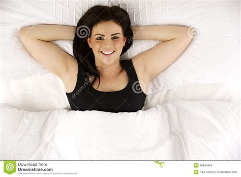 laid in bed woman laid in bed relaxed looking up at the camera smiling