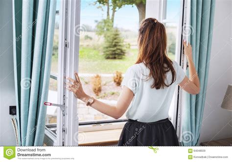 Lifestyle Bedroom Furniture elegant lady opening the bedroom window stock image