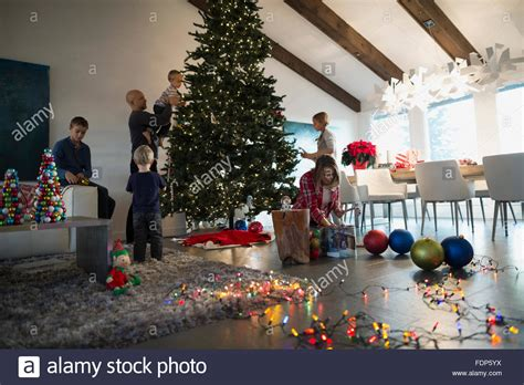family decorating christmas tree in living room stock