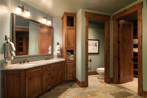 Homes with dark trim bathroom rustic with two sinks dark wood baseboard towel storage