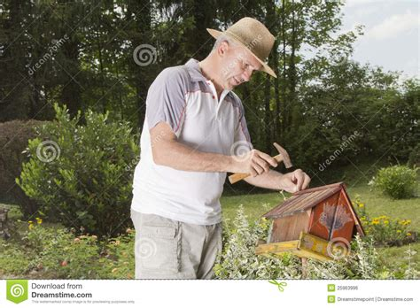 fixing up an old house man fixing old bird house closeup royalty free stock image
