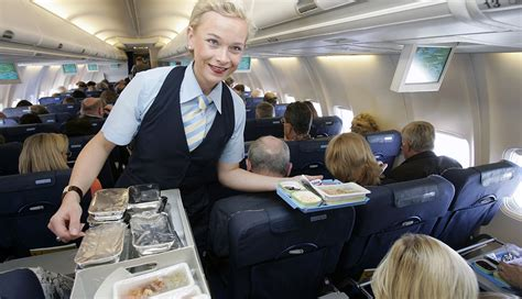 a flight attendant out food trays on plane