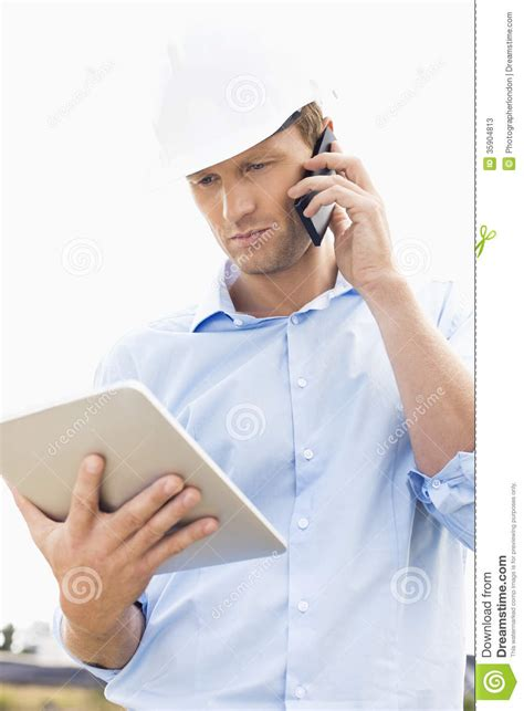 male architect with digital tablet studying plans in male architect writing on clipboard against earthmover at