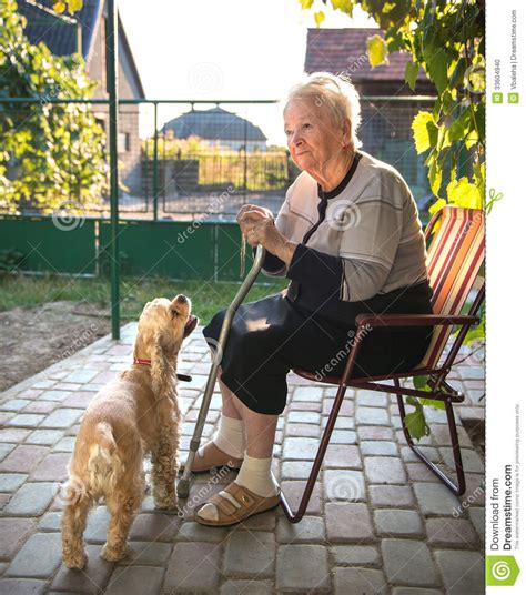 Old woman sitting on a chair with a cane stock photo image 33604940