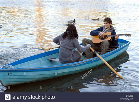 row the boat guitar man playing guitar in row boat stock photo royalty free
