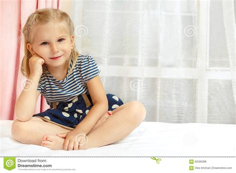 girl sitting on bed little girl sitting on the bed stock photo image 62595396