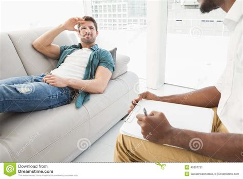 lying on sofa man lying on sofa talking to his therapist stock photo