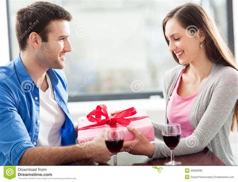 Gift Cards For Young Men - man giving woman gift at cafe stock photo image 30082990