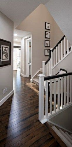 dark wood banister white banister poles with a dark wood handrail and matching stained floor make this