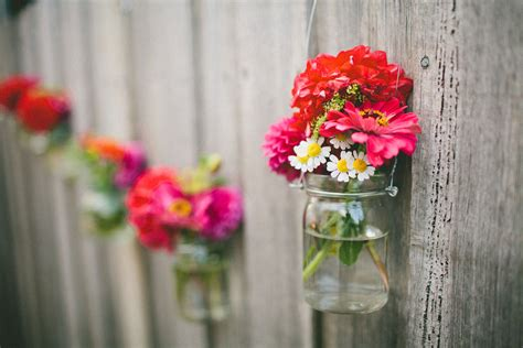 decorating home with flowers hanging jar flowers on outdoor backyard wooden fence for