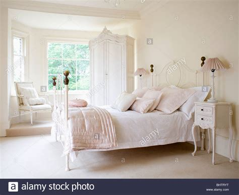 white iron bed pale pink silk quilt and white bedlinen on white wrought
