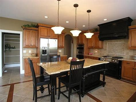 oak cabinets with black island and stove tile floors