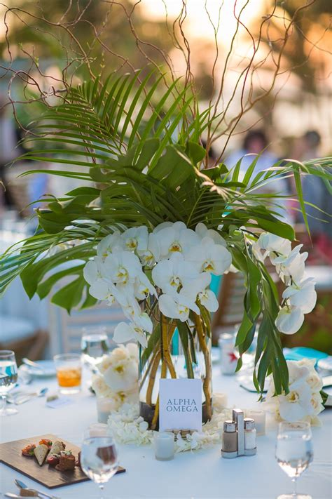 tropical wedding centerpiece with palm leaves monstera