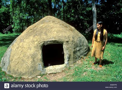cherokee houses traditional cherokee woman in front of a traditional summer house at stock photo