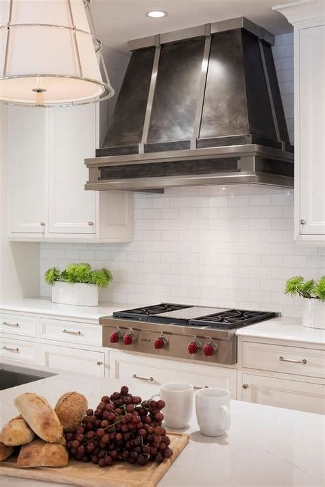 small white kitchen with steel hood dark steel kitchen vent hood with white tiles