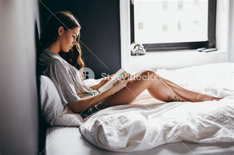 how to read a book in bed side view of beautiful young woman reading book on bed at