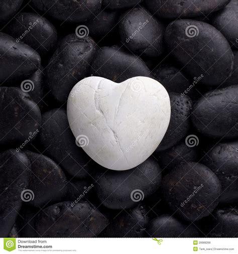 white rock stone in heart shape on black pebble royalty