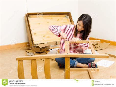 asian using strew driver for assembling furniture