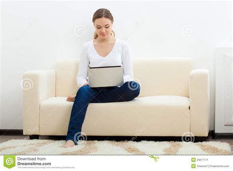 sitting in sofa happy woman sitting on sofa with laptop stock image