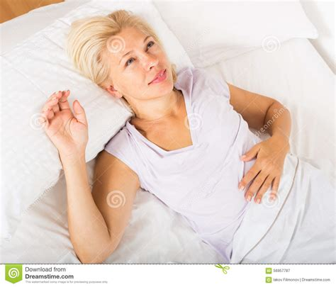 granny bed mature lady in shirt awaking on bed stock photo image