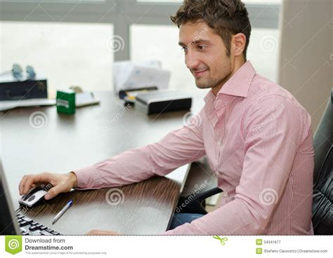Office Worker At Desk Handsome Happy Office Worker Smiling While Using Computer Royalty Free Stock Photography
