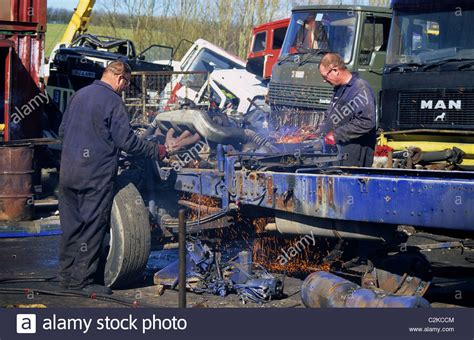 scania truck breakers workmen using cutting torches to dismantle lorry in