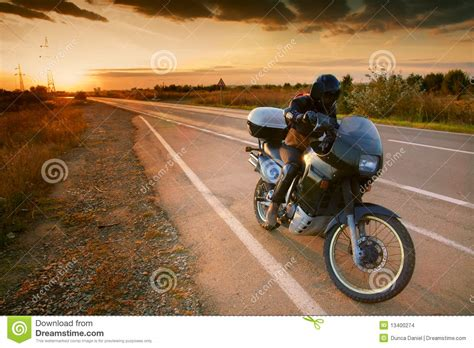 on road motocross biker and motorcycle on road at sunset stock images