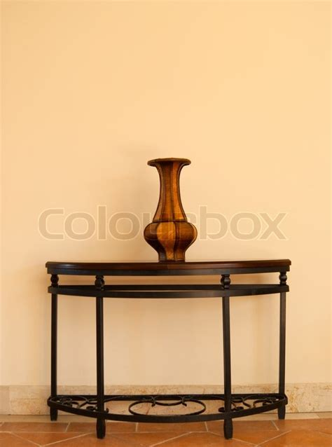 Vase On Table by Beautiful Wooden Vase On Table Near The Wall Stock Photo