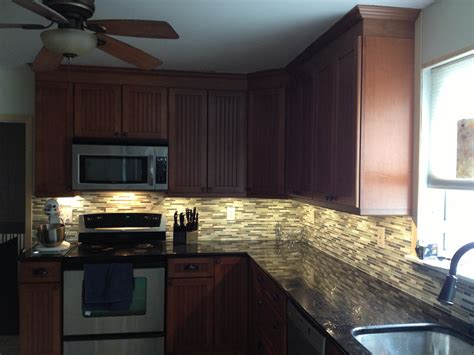 tile under kitchen cabinets kraftmaid maple cinnamon cabinets with black galaxy