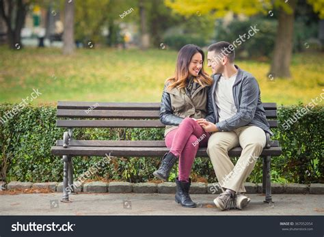 sitting on a park bench song happy young couple love sitting on stock photo 367052054