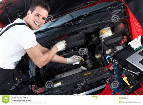 car engine service mechanic checking oil level in a car workshop man in