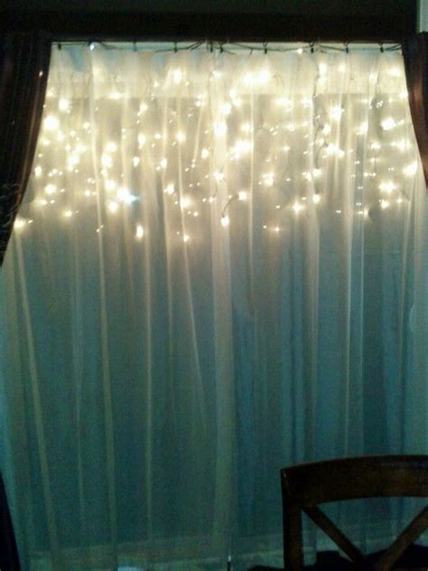 hang icicle lights behind a window sheer looks pretty