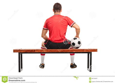 football player on bench football player holding a ball and sitting on a bench stock photo image 60755937