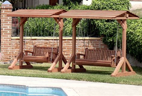 wooden swinging bench garden swing under a small wooden pergola near trees