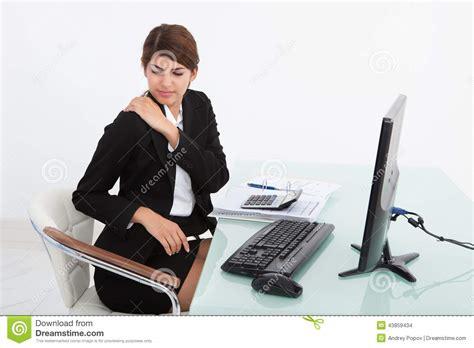 shoulder pain from sitting at desk businesswoman having shoulder pain at computer desk stock