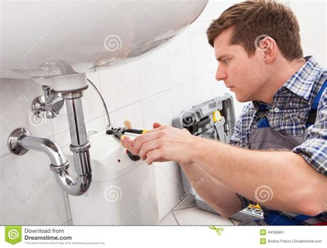 fixing bathroom sink young plumber fixing a sink in bathroom stock image