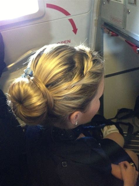 best hairdo for a flight attendant sock bun with loose braid and hawaiian flowers
