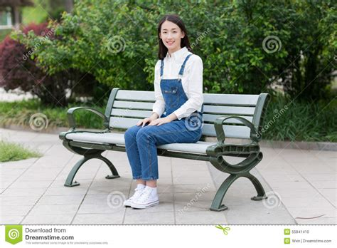 sitting on bench girl sitting on a bench stock photo image 55841410