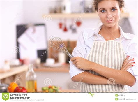 Standing In The Kitchen by Smiling Standing In The Kitchen Stock Photo