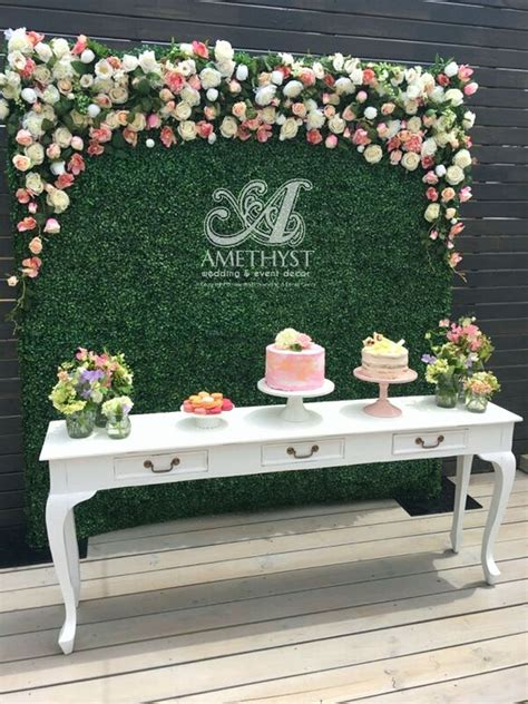 Picture Of boxwood flower wall for a dessert table backdrop