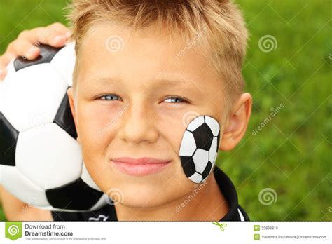 soccer ball with flames boy s face painting by let s young boy with painted face and soccer ball stock photo