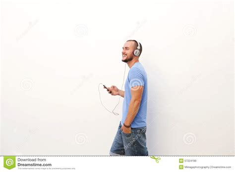 10 songs to listen to when walking the streets of paris project man walking with mobile phone listening to music on