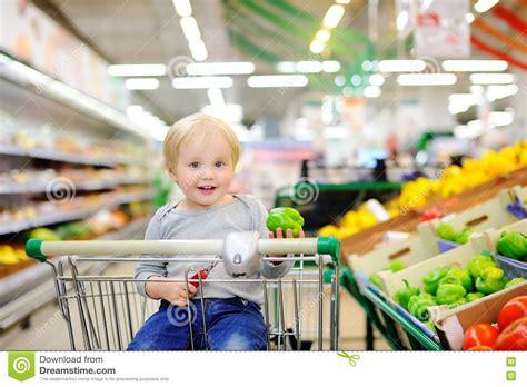 toddler shopping cart toddler boy sitting in the shopping cart in a supermarket