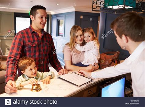 Suzuki Family Support Desk by Family Checking In At Hotel Reception Desk Stock Photo