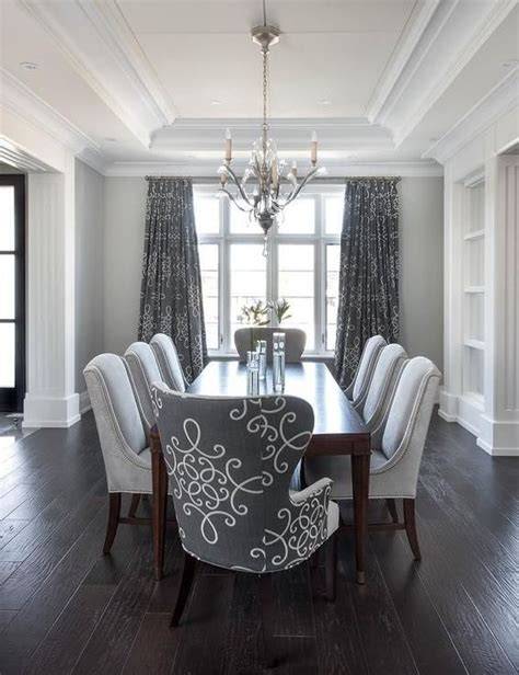 gray dining room features a tray ceiling accented with a