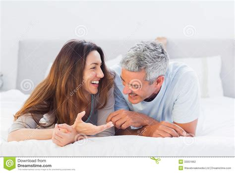 lying on bed talking together stock