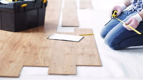 repair building floor and people concept close up of man measuring flooring with ruler and
