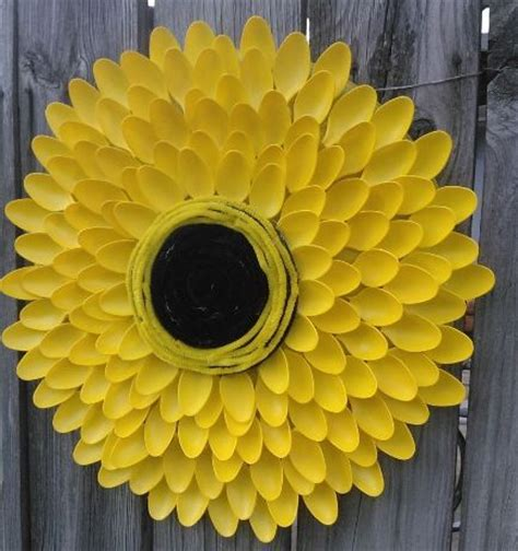 sunflower made from 100 spoons yellow spray paint an serving tray coffee can lid