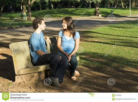 talking bench couple talking on a park bench horizontal stock